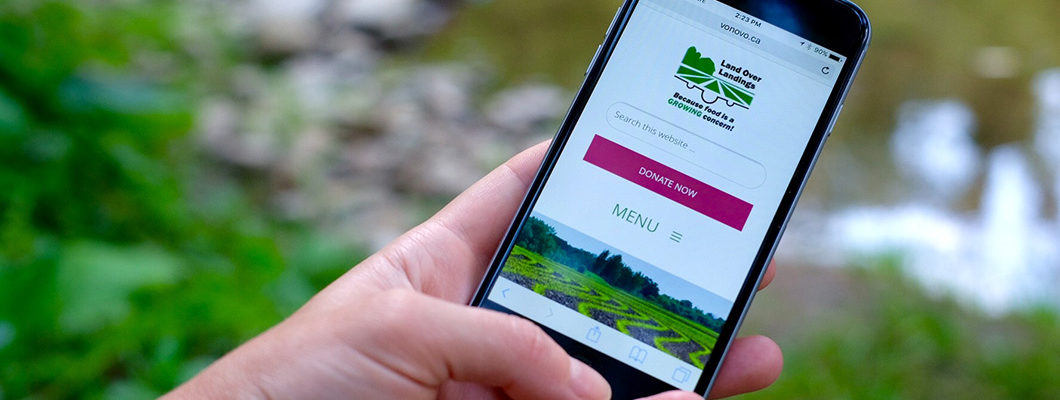 woman holding phone displaying Land Over Landings new website