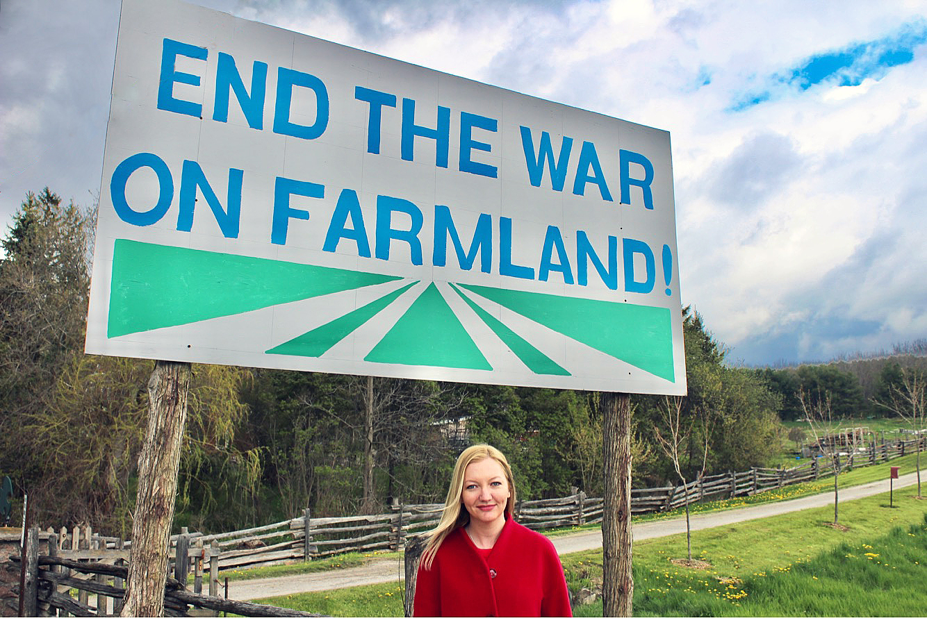 "Photo of MP Jennifer O'Connell infront of a sign reading ""End The War on Farmland"""